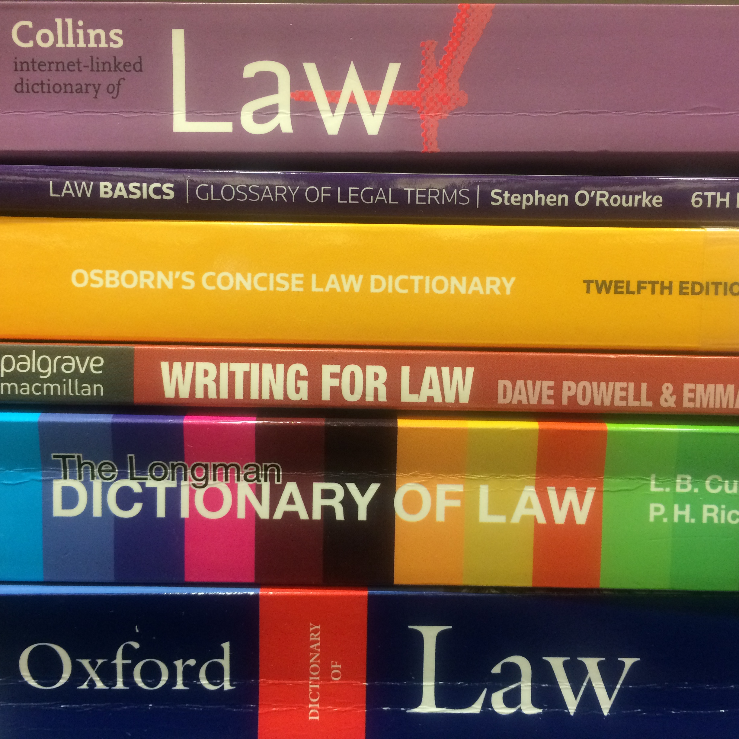 A pile of colouful spines of legal dictionaries and law books