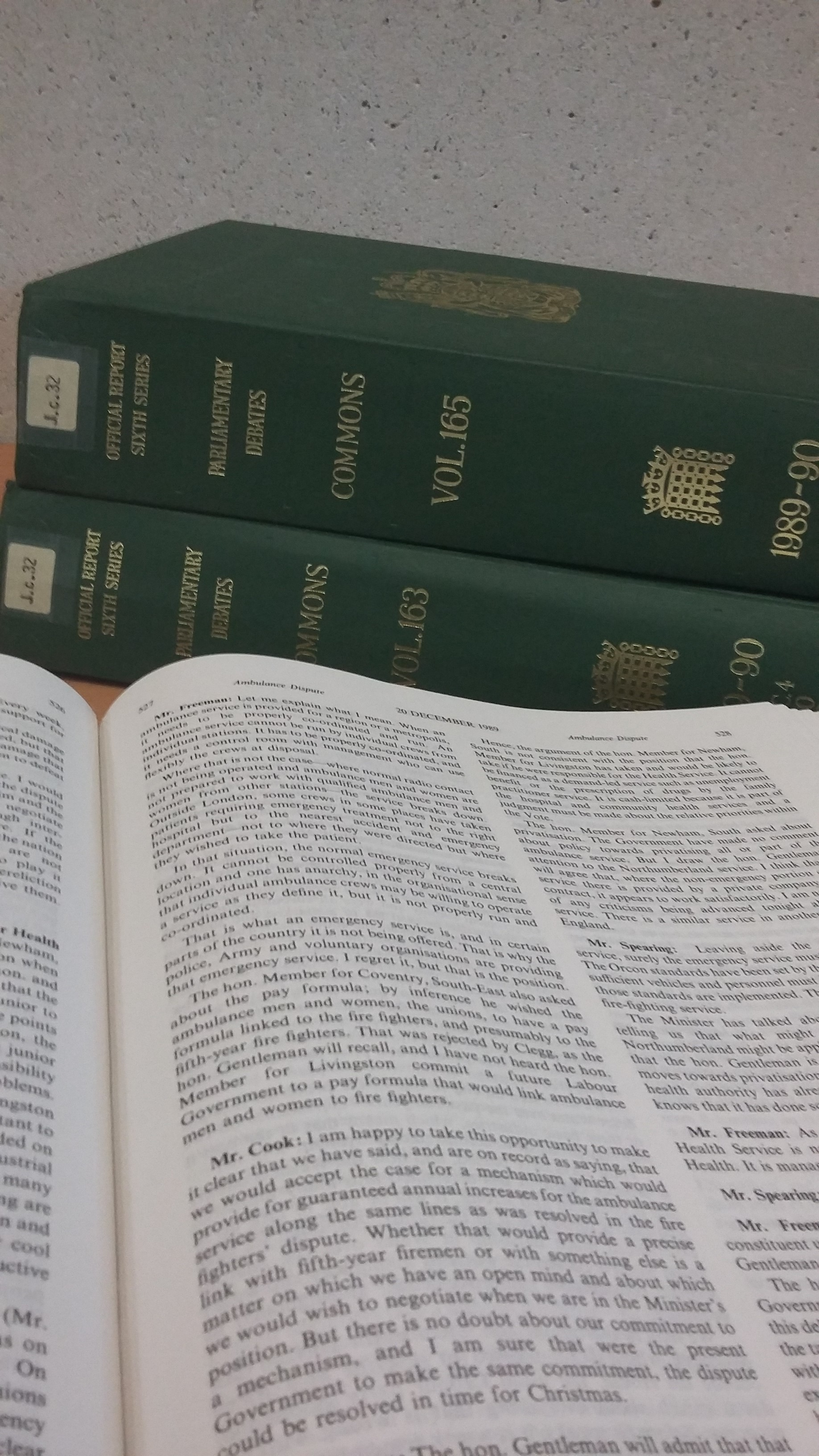 Photo of two green volumes of Hansard (parliamentary debates) with an open volume in front.