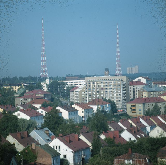 Etualalla taloja ja taka-alalla kaksi radiomastoa.