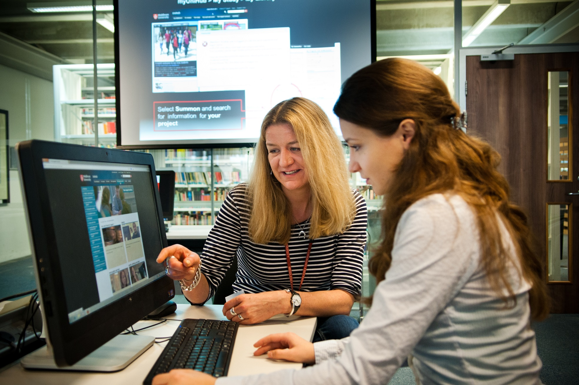 Photo of a student receiving help from a librarian