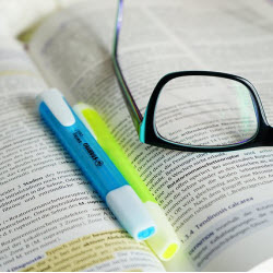 book with glasses and pens