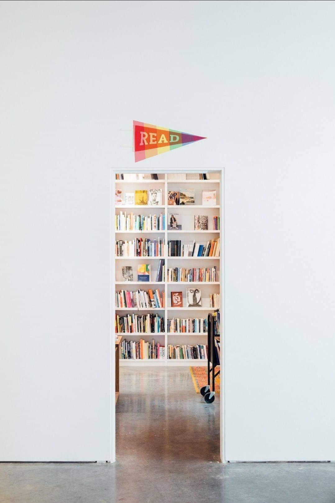 Bookshelves in what looks to be a library, topped with a rainbow flag on which the text 'Read' is displayed