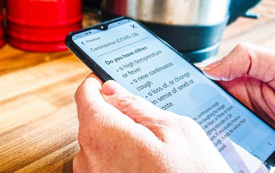 Phone being held showing app