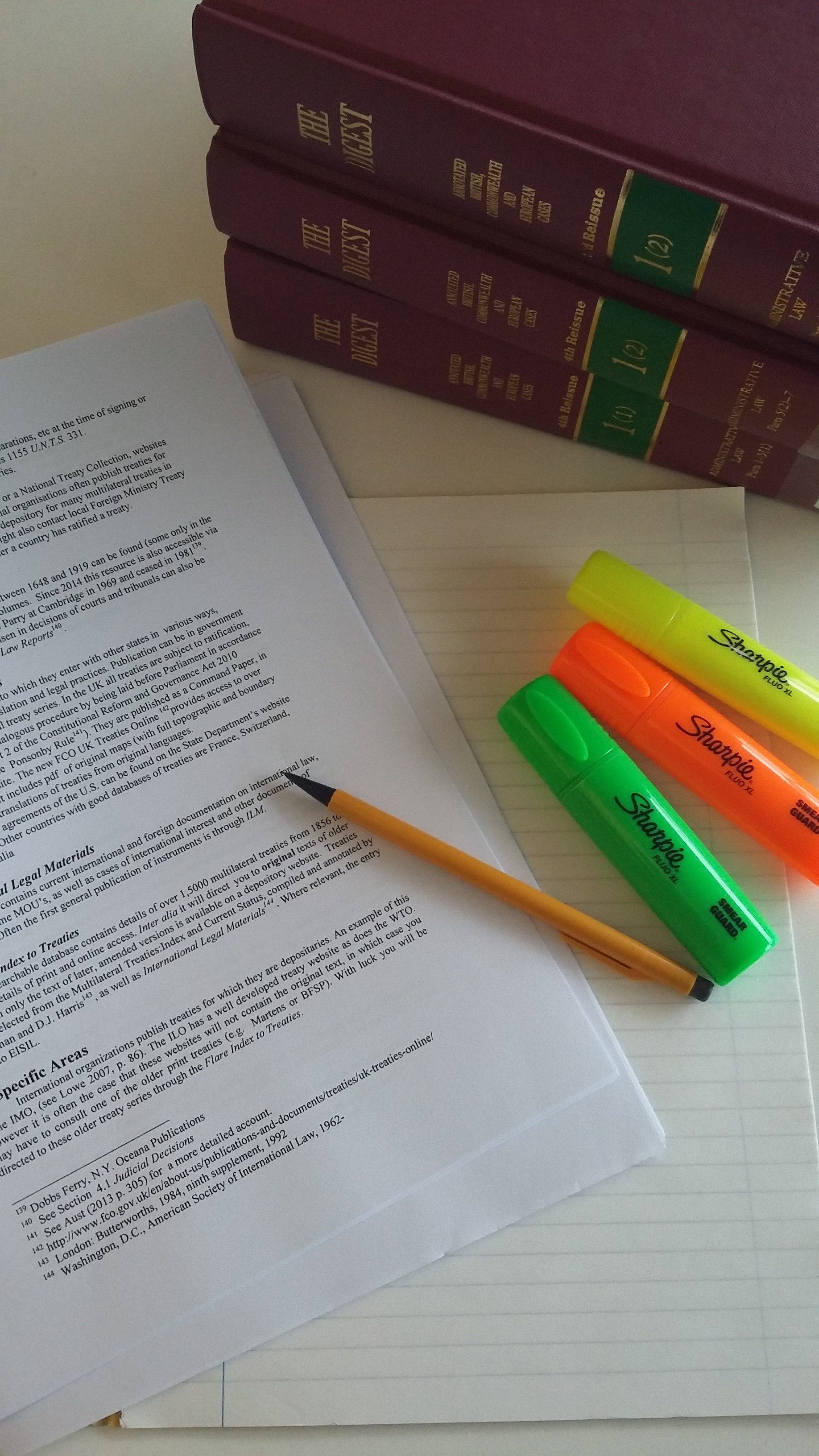 An image of studying - a page of text, highlighter pens and books.
