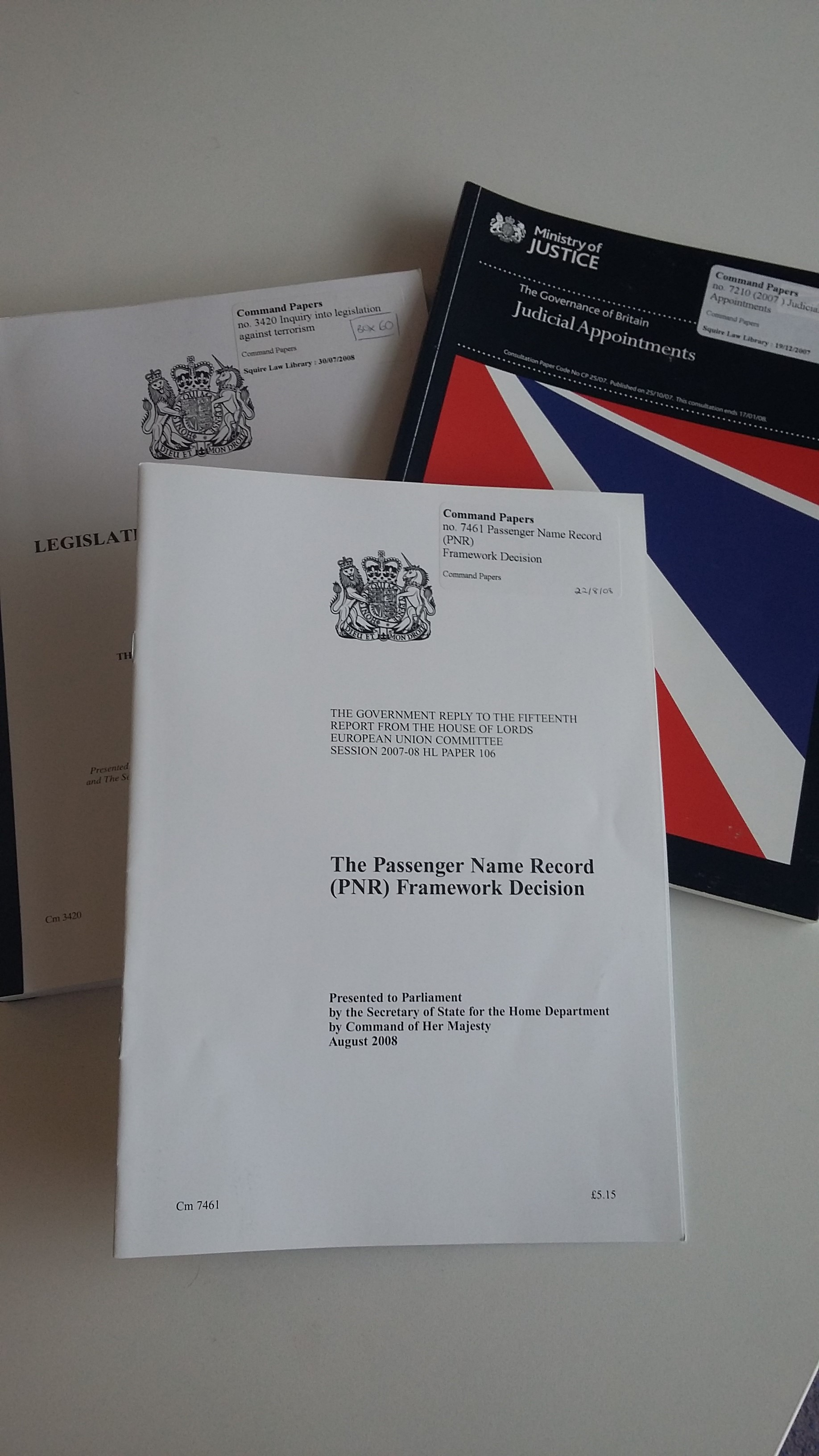 Photo of three parliamentary papers with varying covers on a desk.
