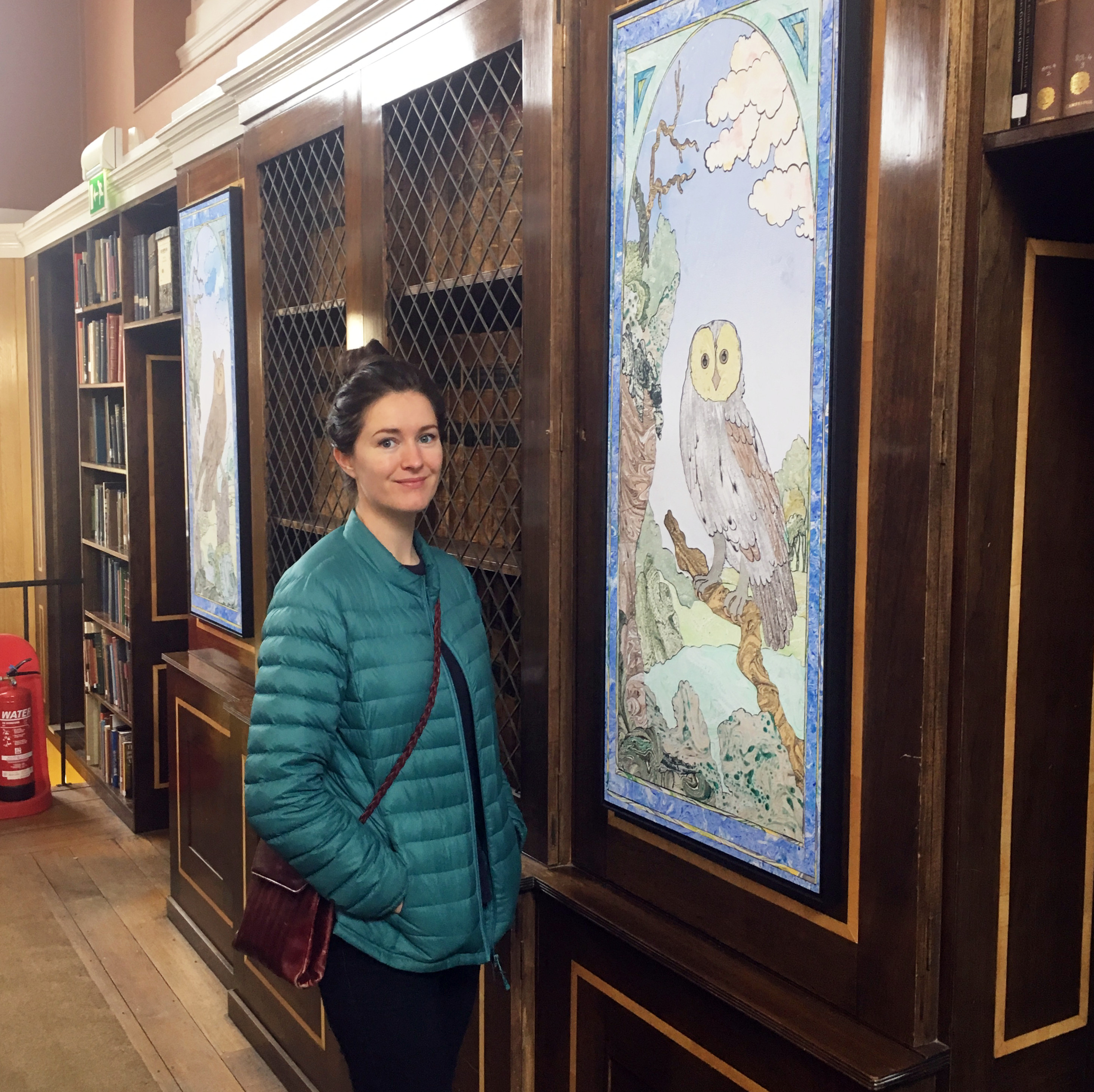 The artist, Erin Hughes, standing next to one of the collages installed in LMH Library