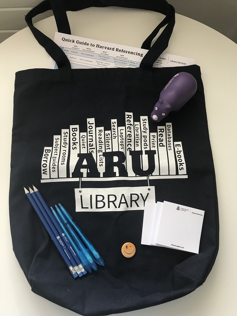 A photo of an ARU Library tote bag with some pens, pencils, stick notes, a squeezy rhino, a smiley badge and a Harvard mini guide.