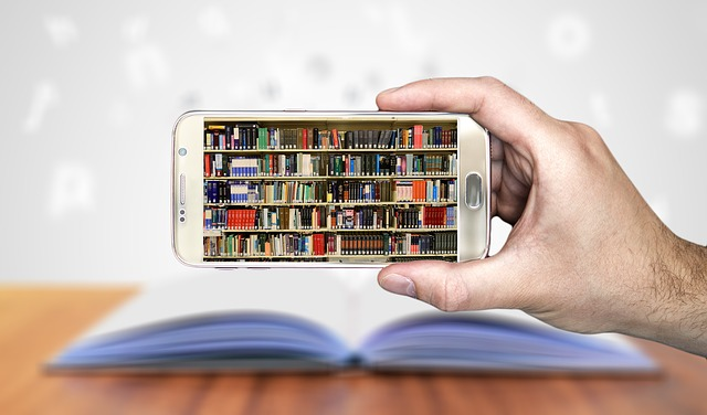 A photo of a phone being held up with shelves of books displayed on the screen.