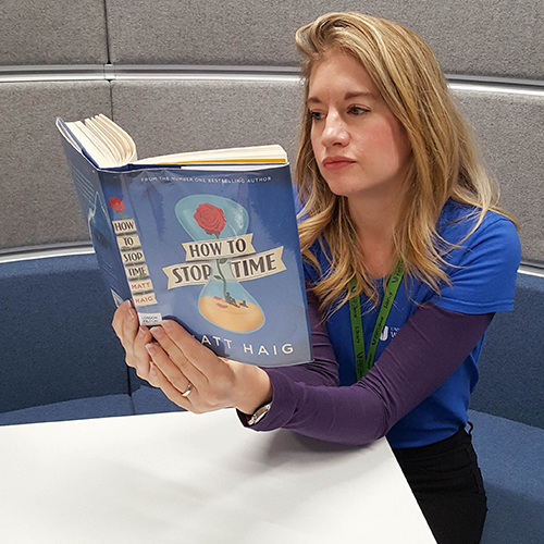 Photograph of Clare reading 'How to Stop Time' by Matt Haig