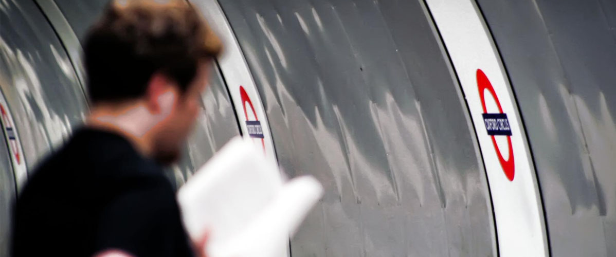 Image of man reading a book on the platform at Oxford Circus tube station.