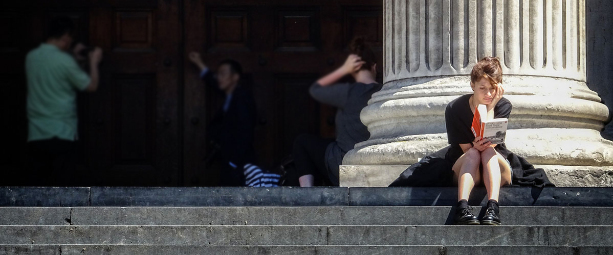 Image of woman reading a book on the steps of Saint Paul's Cathedral.