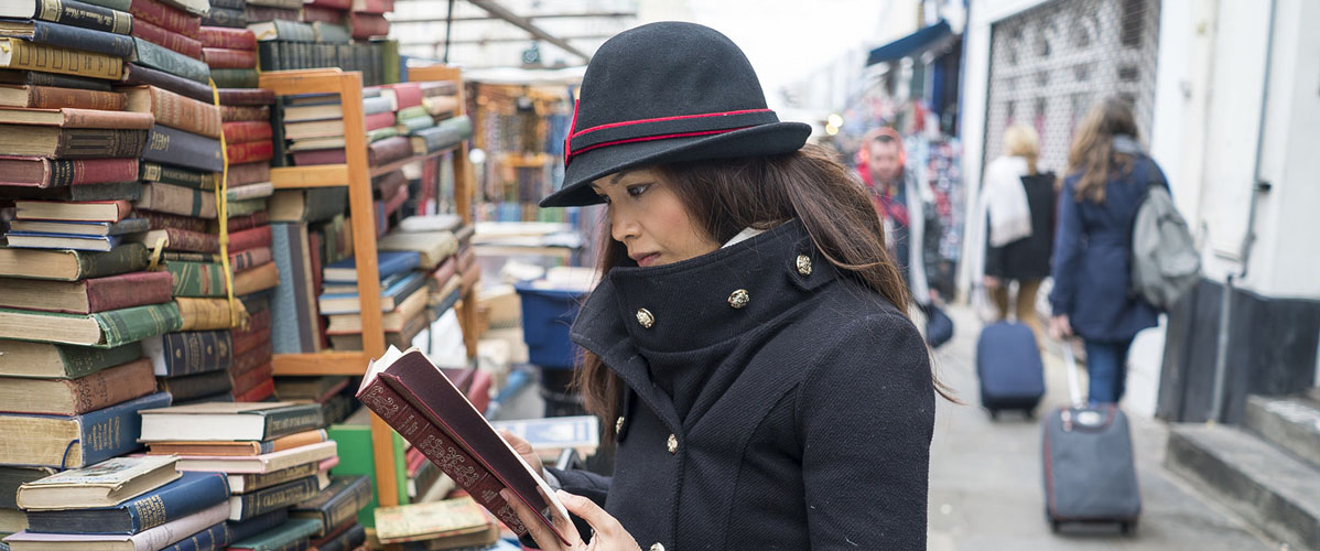 Image of woman looking through books at a stall in Notting Hill market.