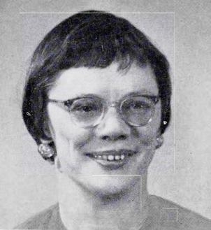 Black and white image of a white woman in plastic rimmed glasses, with short dark hair