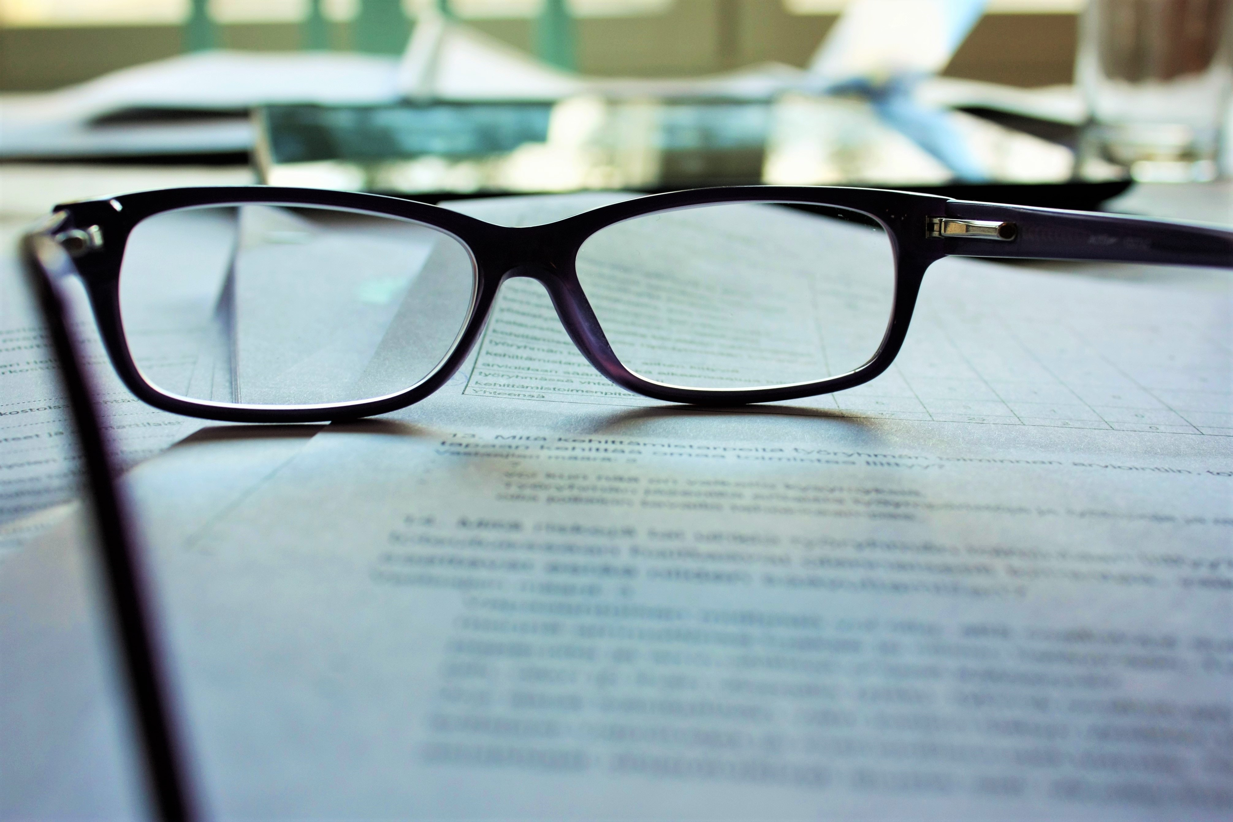 pair of reading glasses on piece of paper
