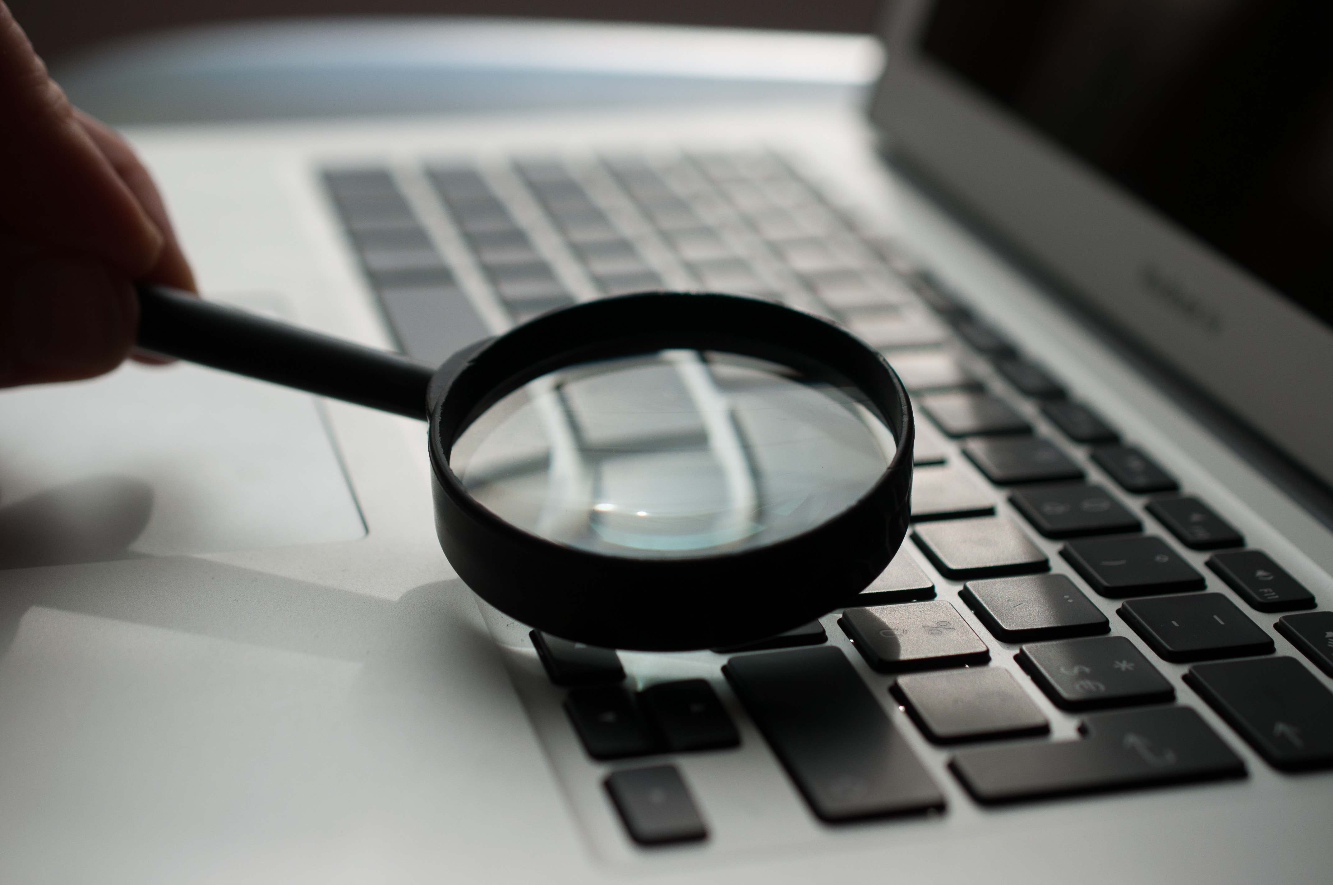 magnifying glass on the keyboard of a laptop