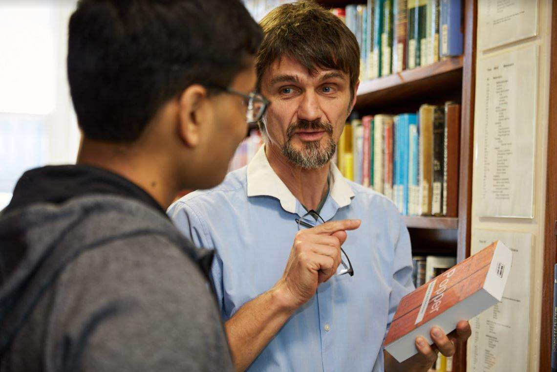 A librarian discusses a book with a student, Sidney Sussex College Library