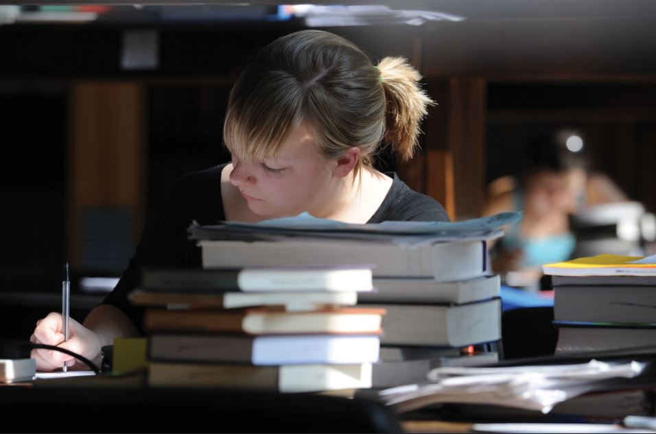 Female student writing in a notebook surrounded by piles of textbooks in a library. Courtesy of Churchill College