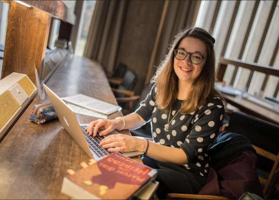Female student working in library on laptop: courtesy of Churchill College