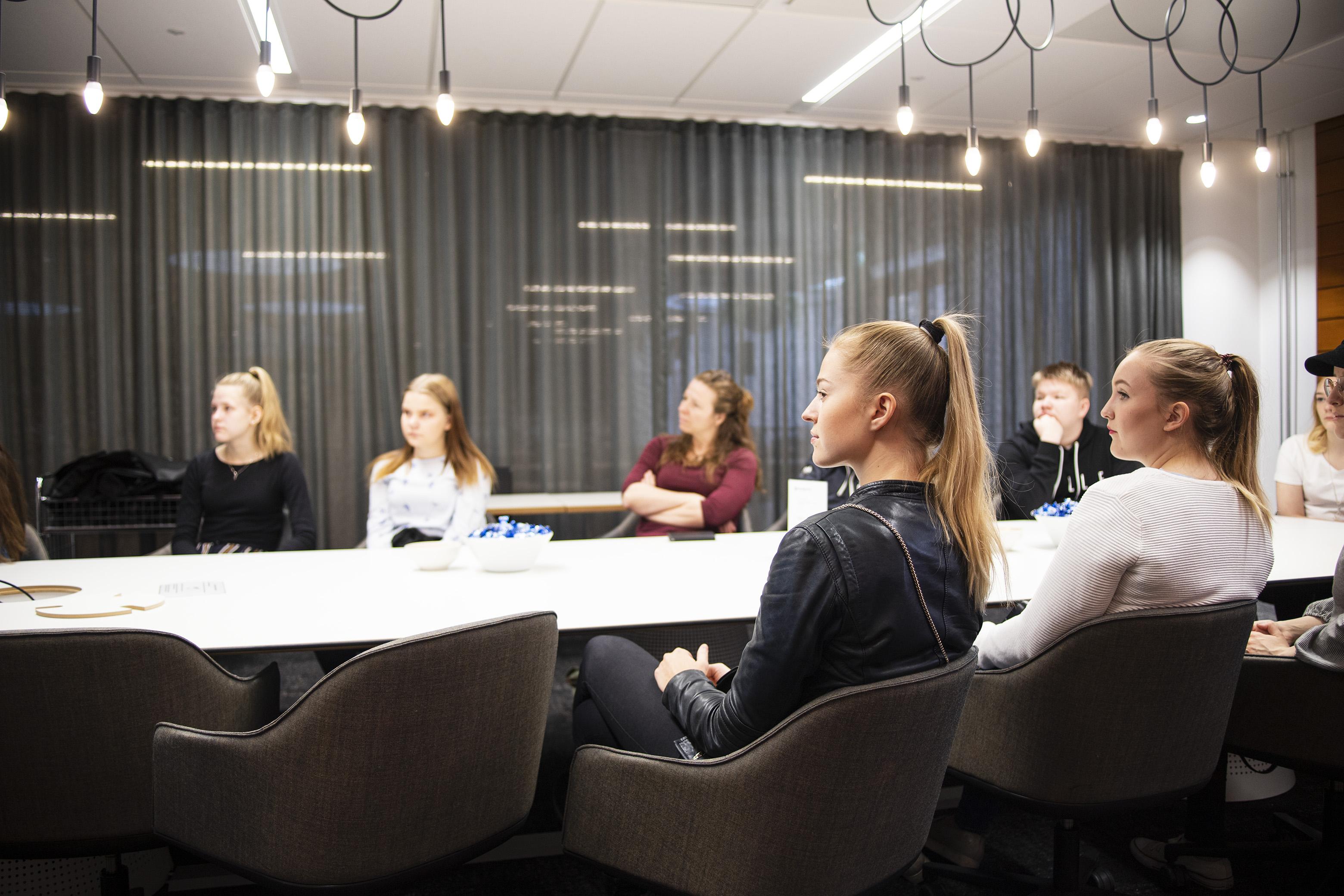 Oppilaita kuuntelemassa esitystä pöydän ympärillä Tilastokeskuksen tiloissa.