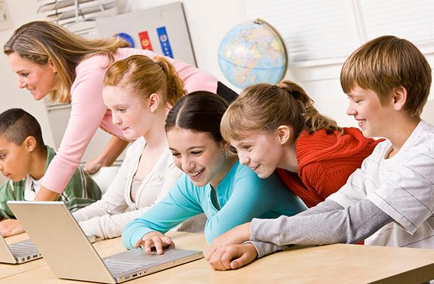 Koululaiset tekevät kannettavalla tietokoneella ryhmätöitä koulussa