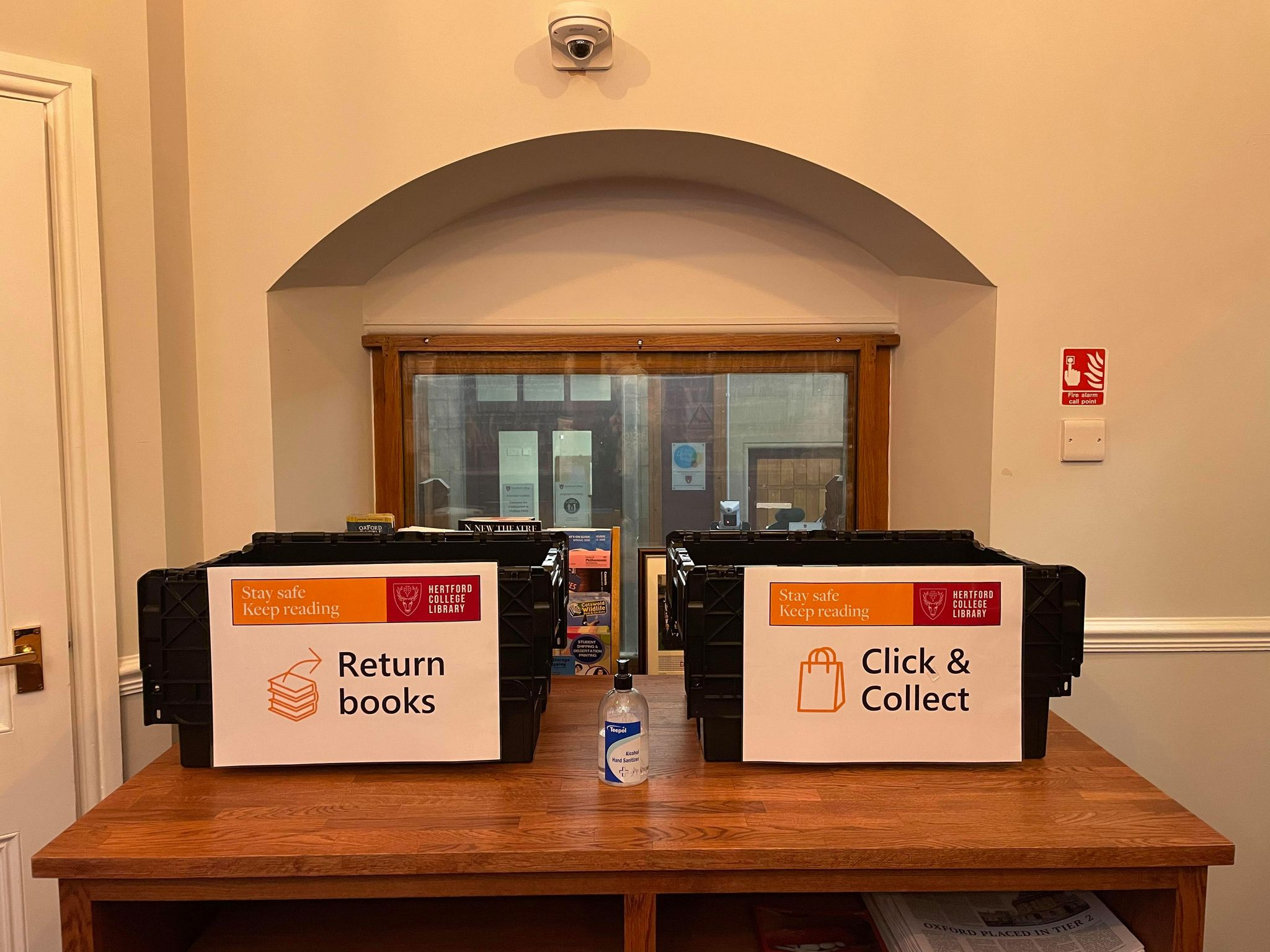 Two black crates in post room for return and collecting library books