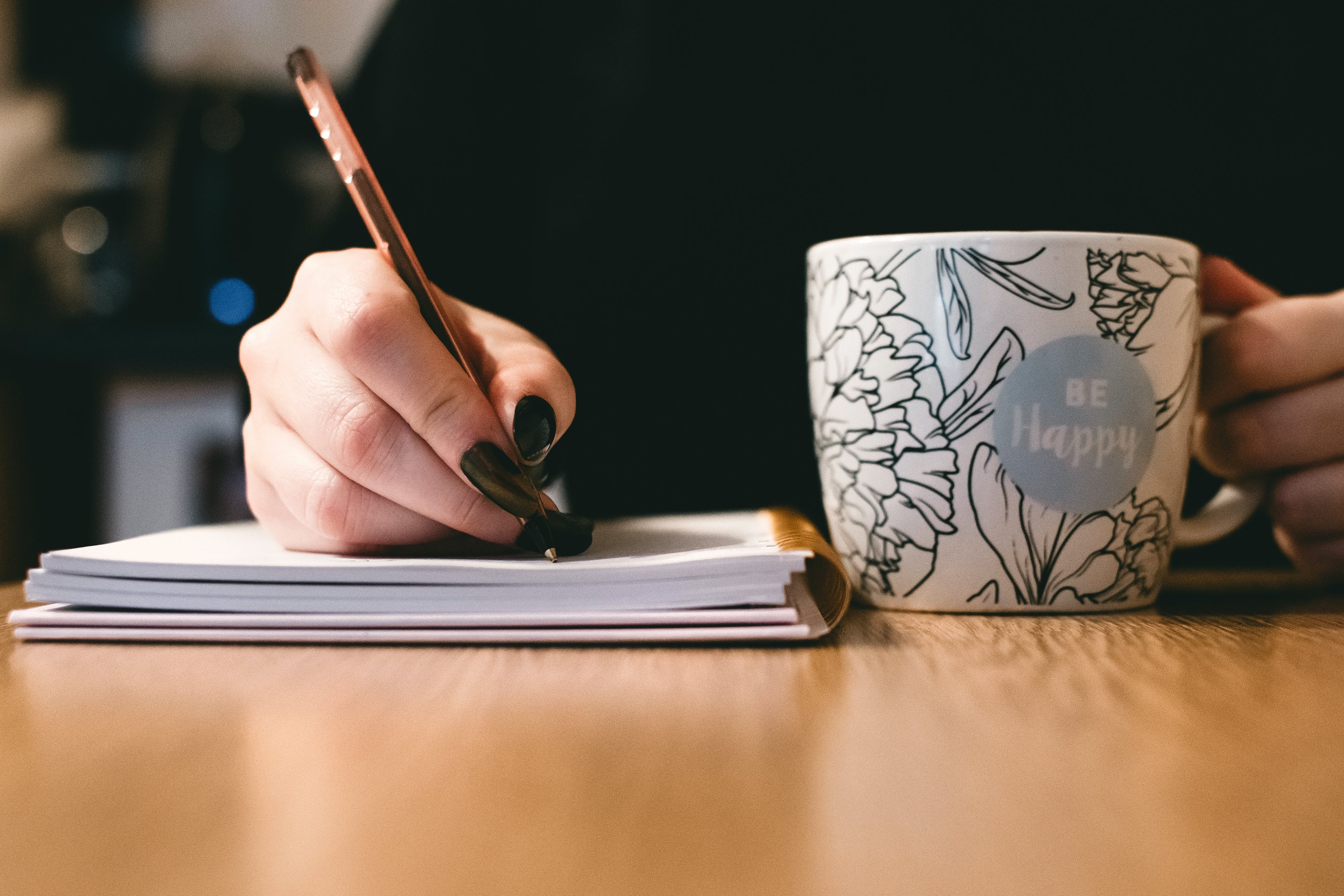person writing with a mug beside them