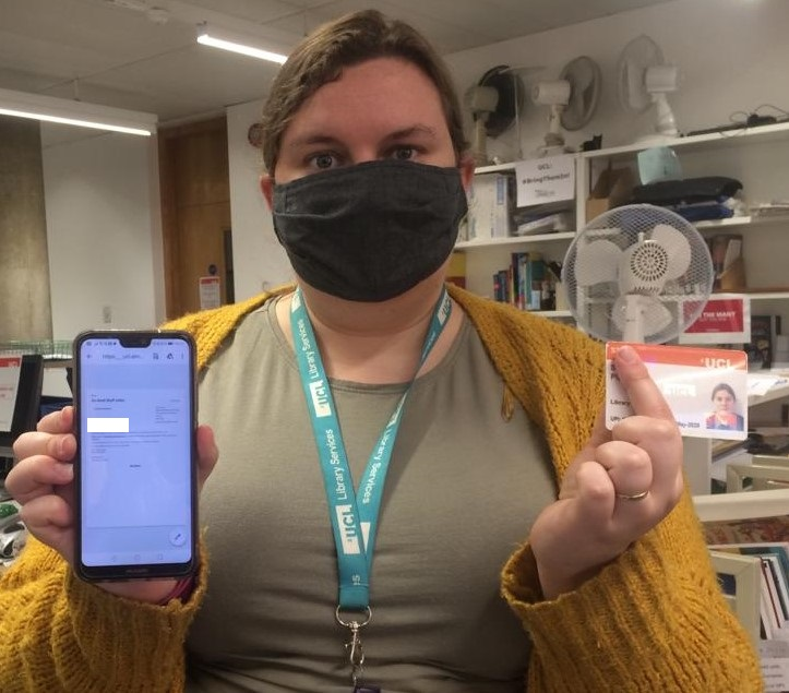 Staff member wearing a mask, showing an email on their phone, and holding their UCL ID card