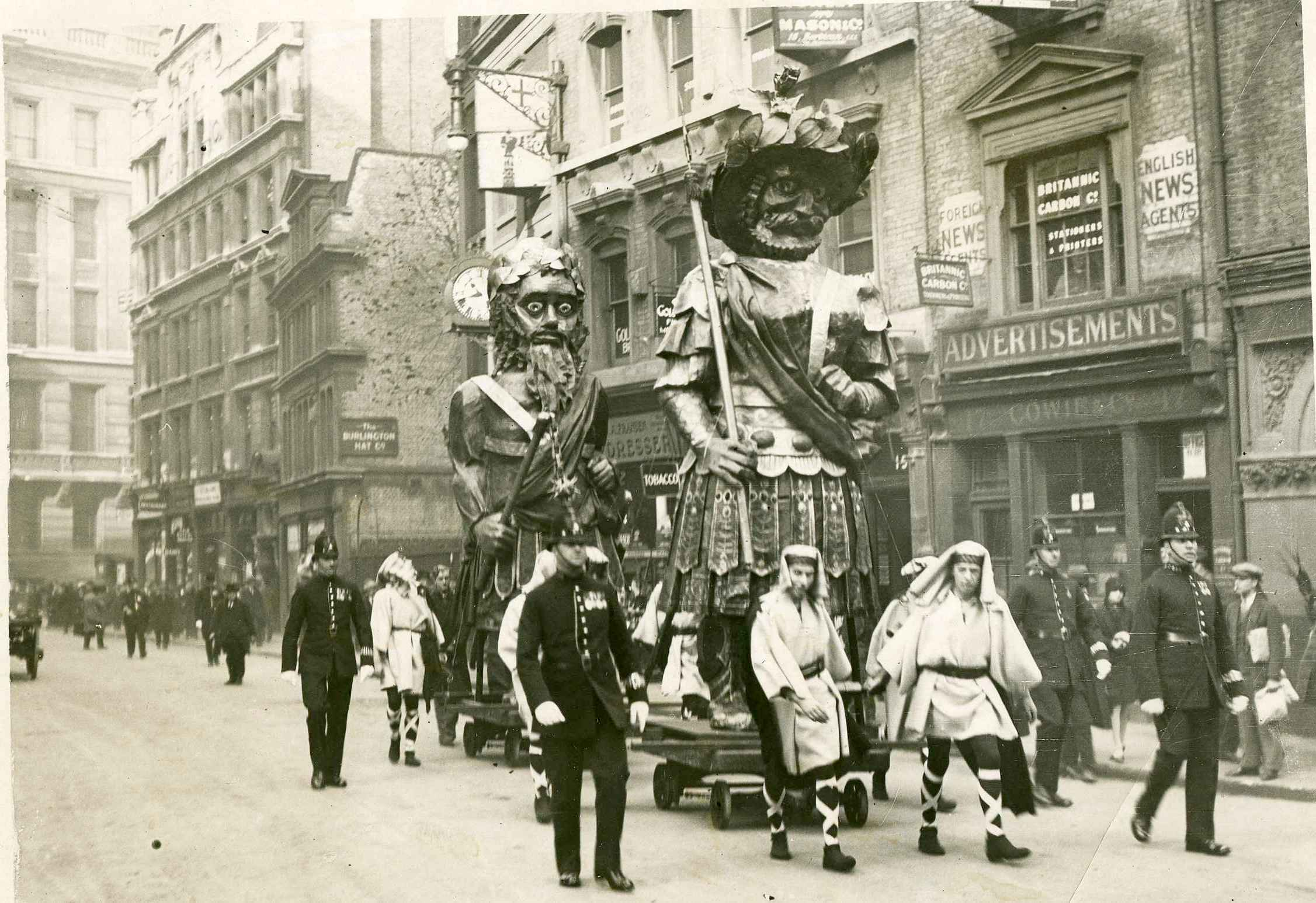 Men in fancy dress wheeling large statues through the streets of London in 1928