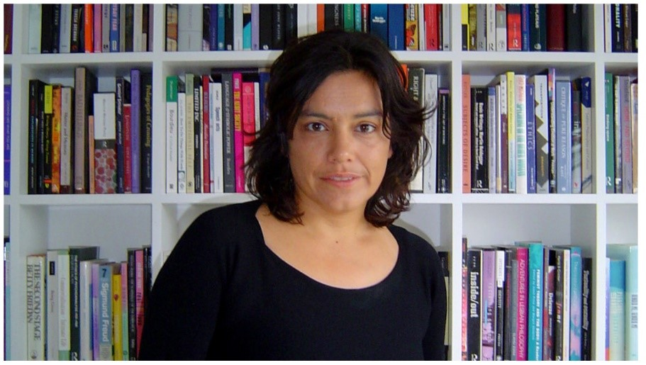 Photo of Sara Ahmed standing in front of a bookshelves