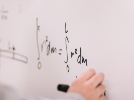 Student writing calculations on a whiteboard. Click for sessions on working with numbers.
