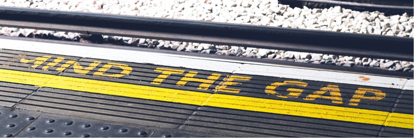 A photograph showing the phrase 'Mind the Gap' painted on a railway platform.