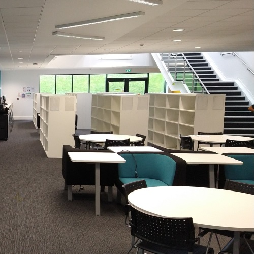 View of the left side of the new Library space with empty shelves and seating in the foreground