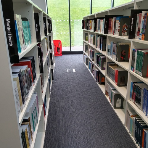 View along two aisles of books which have been reshelved along with subject markers
