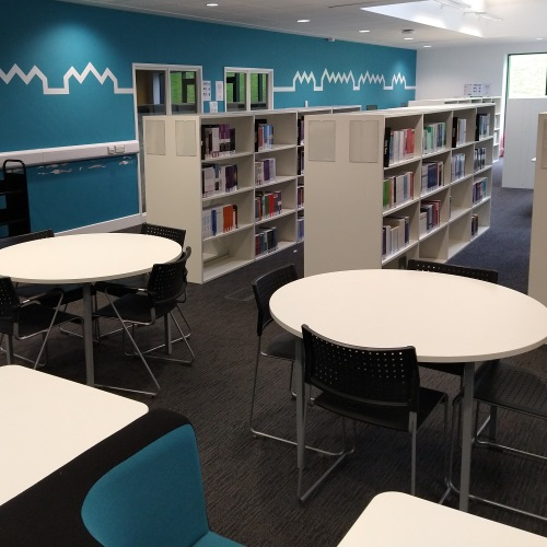 Photo of group study tables and individual study soft seating, with Library shelves in the background