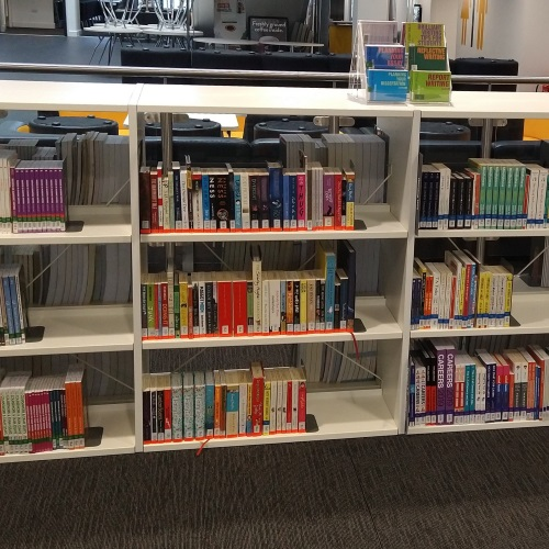 Image of Study Skills and Fiction books on low-level shelves, with cafe and foyer areas in background