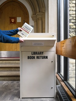 A photograph of a reader dropping a book into the return box.