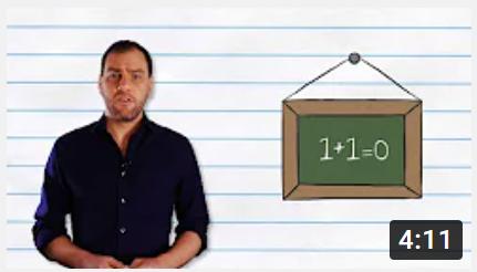"""Adult man beside chalkboard """"1+1=0"""""""