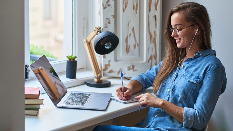 Female student working at home at a desk in sunlight