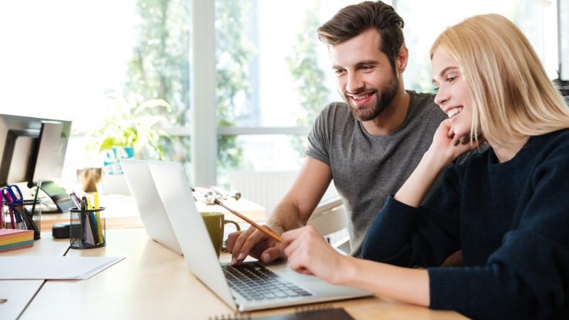 Smiling couple sat at desk