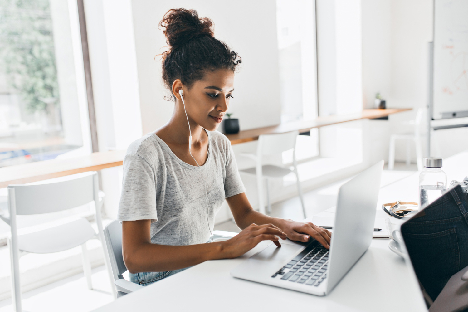 Black female student using a laptop in a bright room