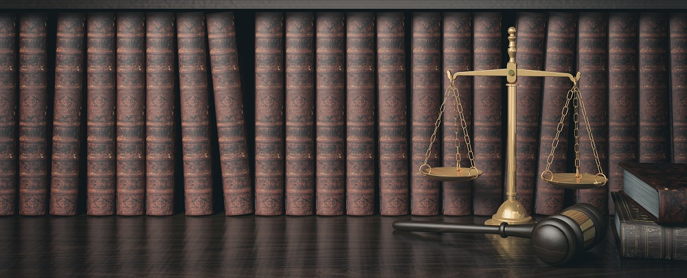 Scales and gavel in front of a legal bookshelf