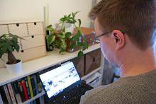 Mies katsoo kannettavaa tietokonetta kirjahyllyn edessä.