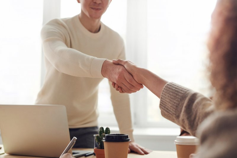 Photo of two people shaking hands across a table with a laptop and travel coffee cups on it.
