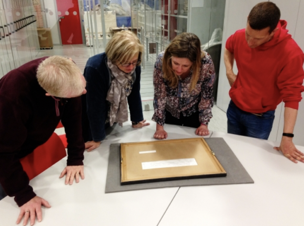 A group of four people looking over an artwork on a table.