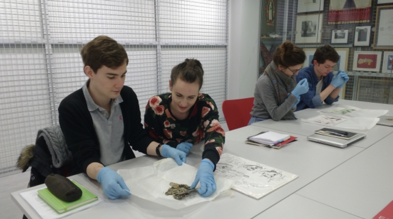 Students in a table with gloves on handling artworks