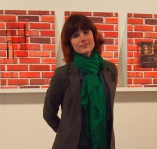 Woman standing in front of artwork looks directly at camera
