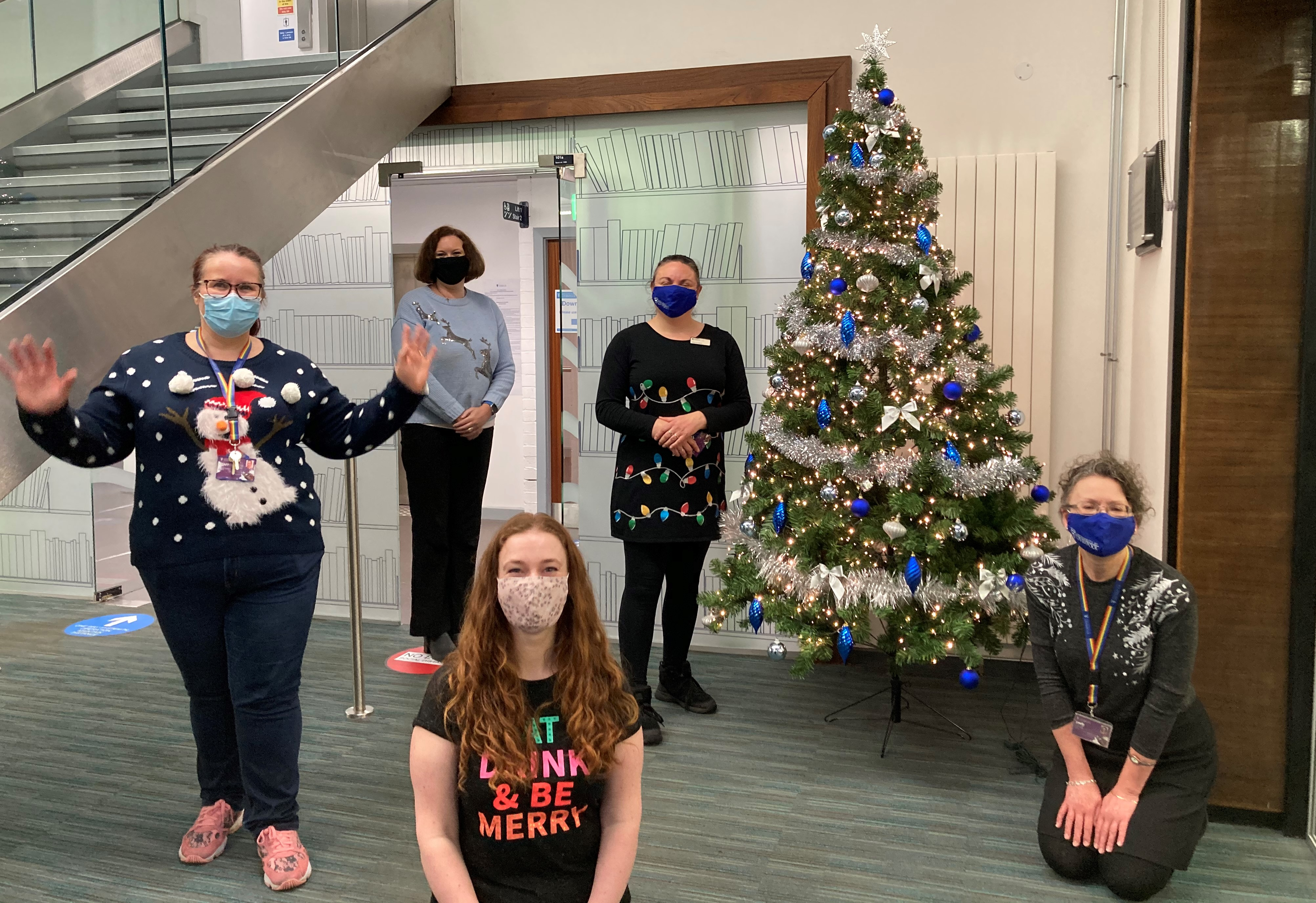 Library staff in Christmas jumpers and face masks in front of Christmas Tree