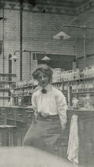 Black and white photograph of a woman sitting in a chemistry laboratory of the Royal Technical College c.1910. Woman is Miss M. M. J. Sutherland.