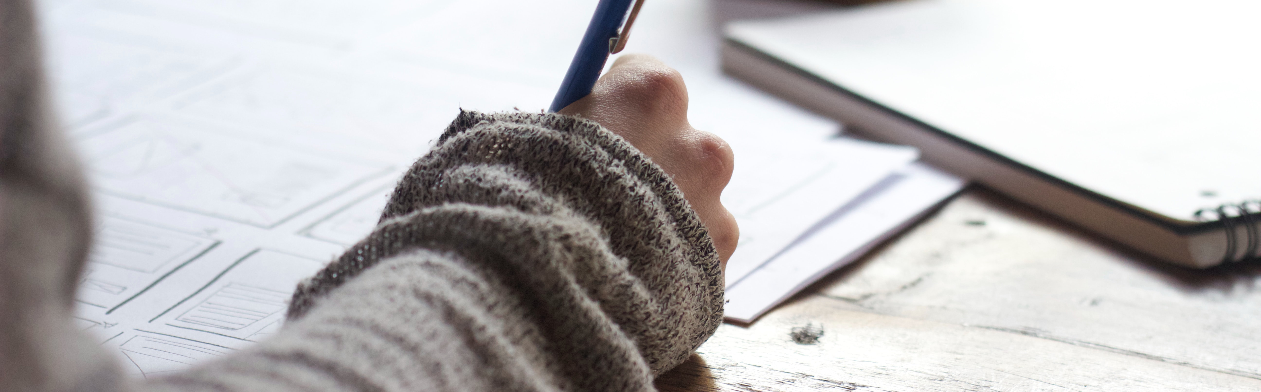 Photo of a hand holding a pen, writing and drawing at a desk