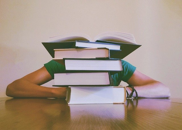 Person leaning on desk with a pile of books covering their face.